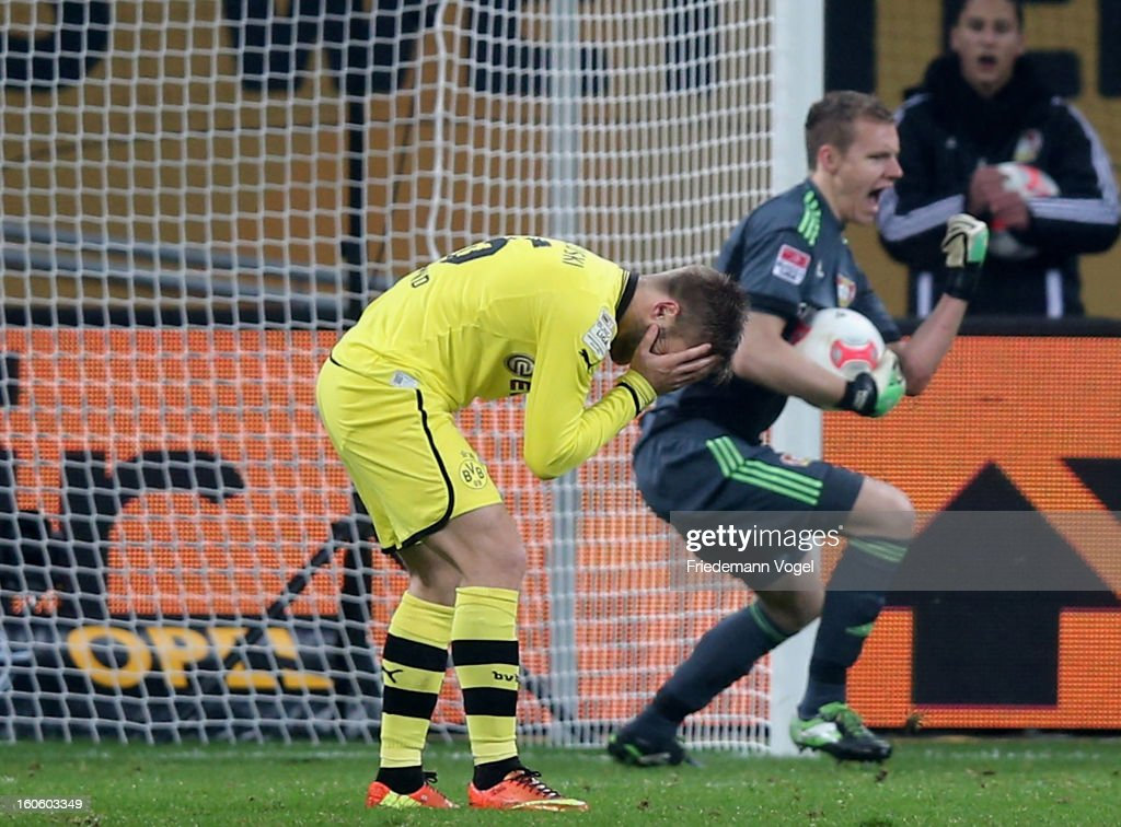 Jakub Kuba Blaszczykowski (L) of Dortmund reacts after missing a penalty against Bernd Leno of Leverkusen (R) during the Bundesliga match between Bayer 04 Leverkusen and Borussia Dortmund at BayArena on February 3, 2013 in Leverkusen, Germany.
