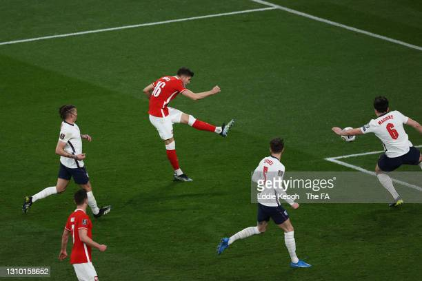 Jakub Moder of Poland scores their side's first goal whilst under pressure from Harry Maguire of England during the FIFA World Cup 2022 Qatar...