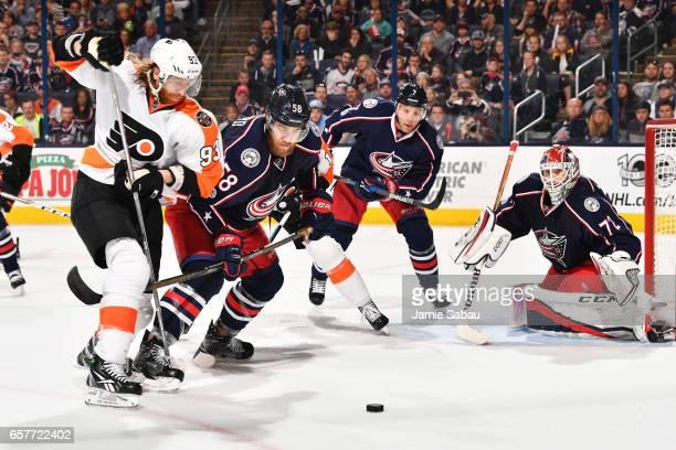 Jakub Voracek of the Philadelphia Flyers and David Savard of the Columbus Blue Jackets battle for a loose puck as goaltender Sergei Bobrovsky of the...