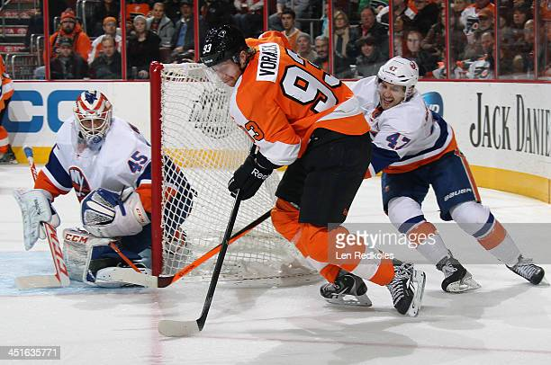 Jakub Voracek of the Philadelphia Flyers attempts a scoring chance against goaltender Anders Nilsson of the New York Islanders while being defended...