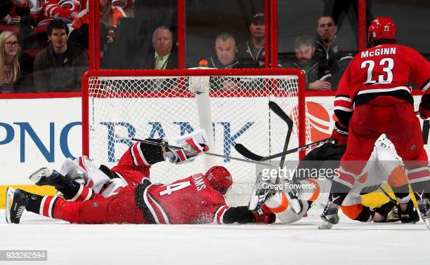 Jakub Voracek of the Philadelphia Flyers backhands the puck past the defense of Justin Williams of the Carolina Hurricanes and teammate goaltender...
