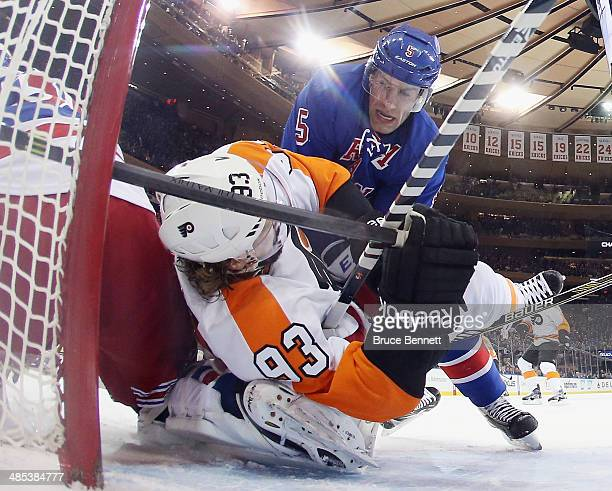 Jakub Voracek of the Philadelphia Flyers is taken down in the crease by Dan Girardi of the New York Rangers during the first period in Game One of...