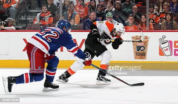 Jakub Voracek of the Philadelphia Flyers takes a slapshot against Nick Holden of the New York Rangers on November 25 2016 at the Wells Fargo Center...