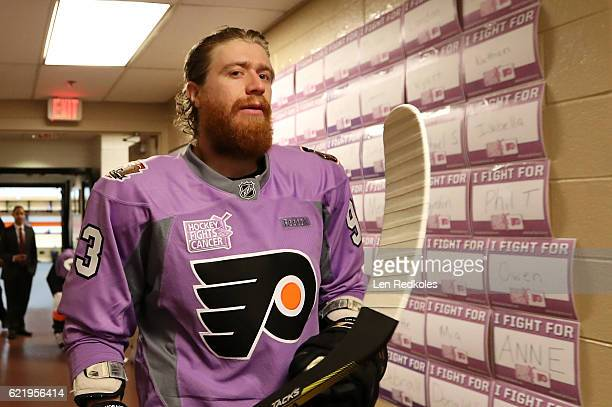 Jakub Voracek of the Philadelphia Flyers walks through a hallway towards the ice surface that has been filled with dozens of 'I Fight For' placards...