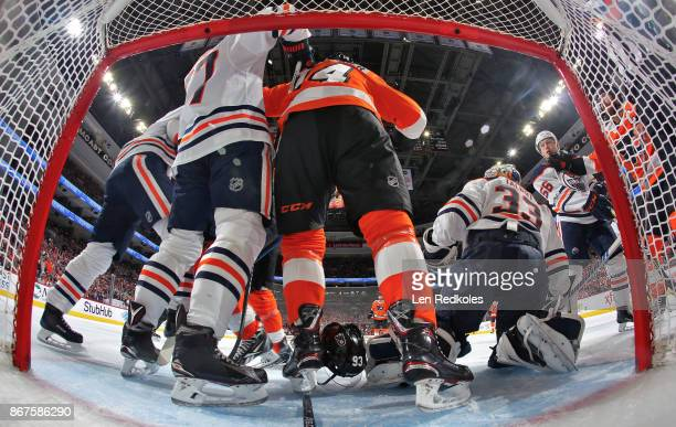 Jakub Voracek Sean Couturier and Claude Giroux of the Philadelphia Flyers battle in the crease against Oscar Klefom Cam Talbot and Kailer Yamamoto of...