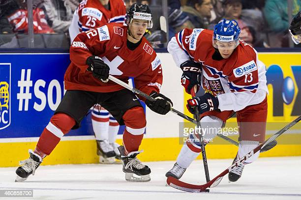 Jakub Vrana of Czech Republic moves the puck against Jason Fuchs of Switzerland during the 2015 IIHF World Junior Championship on December 27 2014 at...