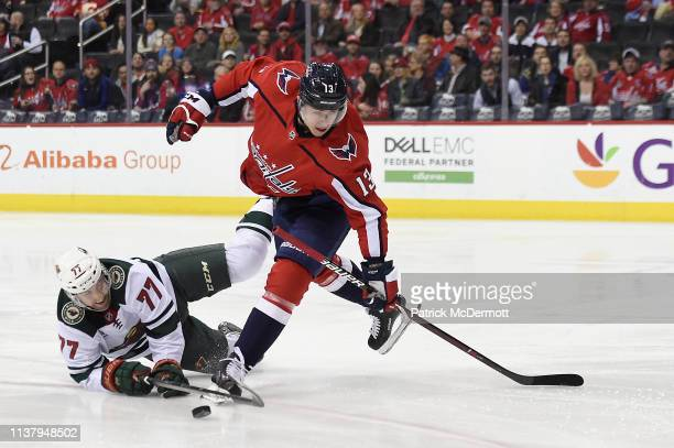 Jakub Vrana of the Washington Capitals and Brad Hunt of the Minnesota Wild battle for the puck in the first period at Capital One Arena on March 22...
