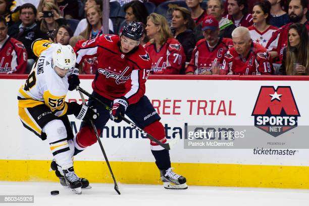 Jakub Vrana of the Washington Capitals and Kris Letang of the Pittsburgh Penguins battle for the puck in the third period at Capital One Arena on...