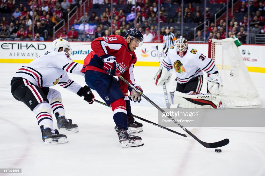 Jakub Vrana #13 of the Washington Capitals controls the puck against Brent Seabrook #7 of the Chicago Blackhawks in the first period at Capital One Arena on December 6, 2017 in Washington, DC.