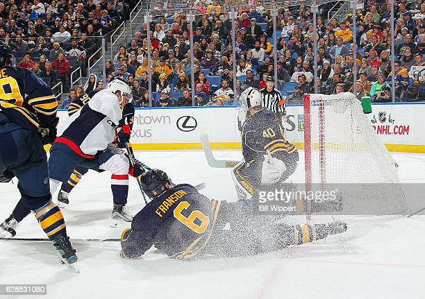 Jakub Vrana of the Washington Capitals scores his first career NHL goal against Robin Lehner and Cody Franson of the Buffalo Sabres during an NHL...