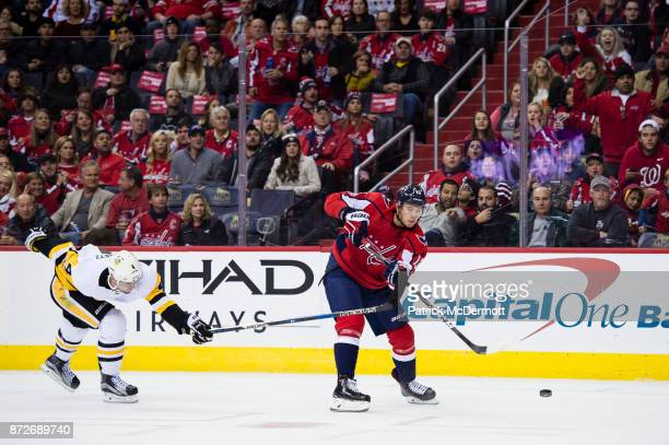 Jakub Vrana of the Washington Capitals shoots and scores an empty net goal against Justin Schultz of the Pittsburgh Penguins in the third period at...