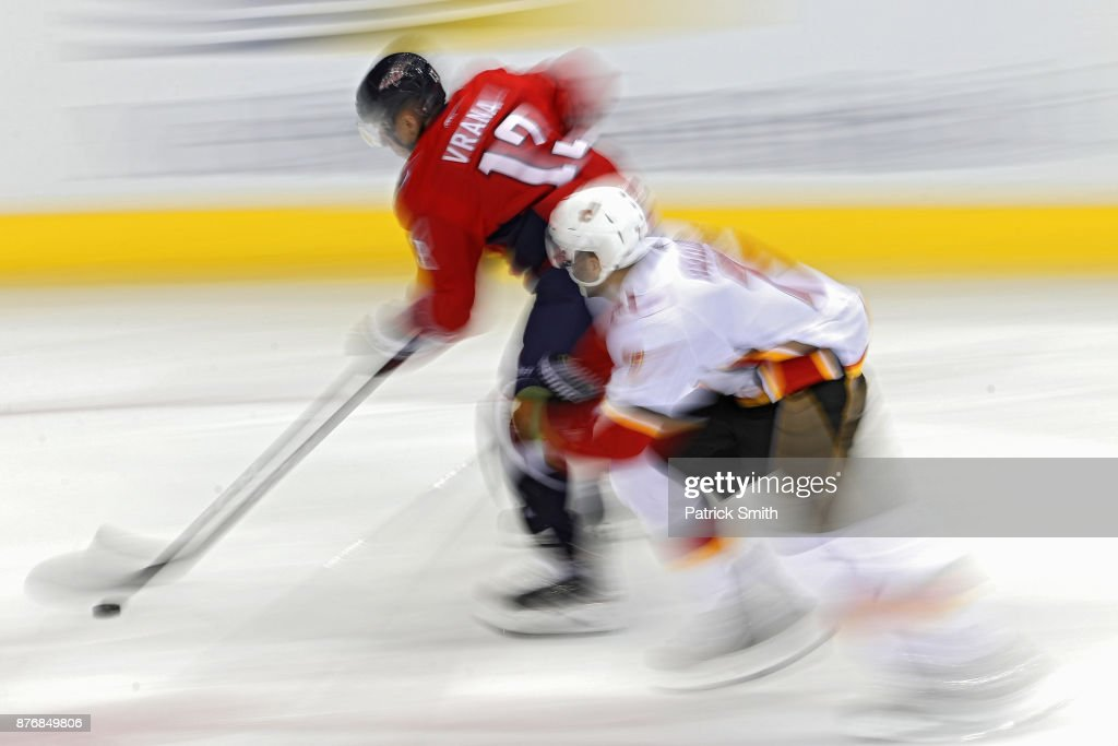 Jakub Vrana #13 of the Washington Capitals skates past TJ Brodie #7 of the Calgary Flames during the first period at Capital One Arena on November 20, 2017 in Washington, DC.