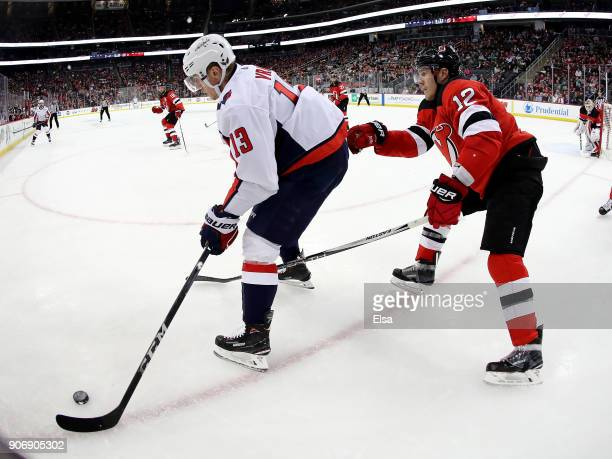 Jakub Vrana of the Washington Capitals tries to keep the puck from Ben Lovejoy of the New Jersey Devils in the third period on January 18 2018 at...