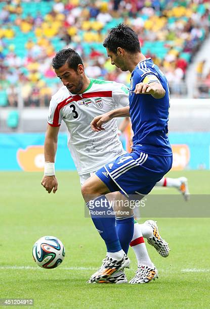 Jalal Hosseini of Iran and Emir Spahic of Bosnia and Herzegovina compete for the ball during the 2014 FIFA World Cup Brazil Group F match between...