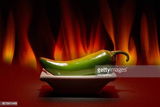Jalapeno pepper on a plate in front of flames