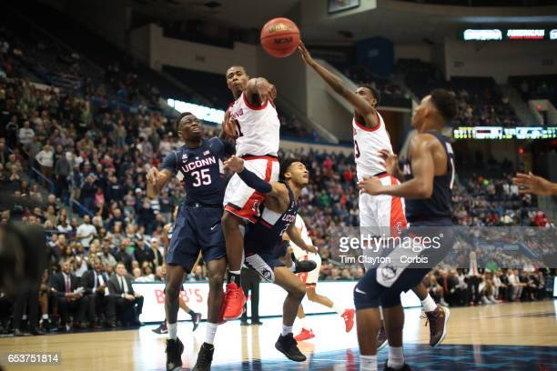 Jalen Adams of the Connecticut Huskies drives to the basket defended by Gary Clark of the Cincinnati Bearcats and Nysier Brooks of the Cincinnati...