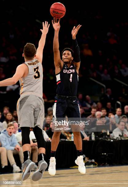 Jalen Adams of the Connecticut Huskies takes a shot as Jordan Bohannon of the Iowa Hawkeyes defends during the championship game of the 2K Empire...