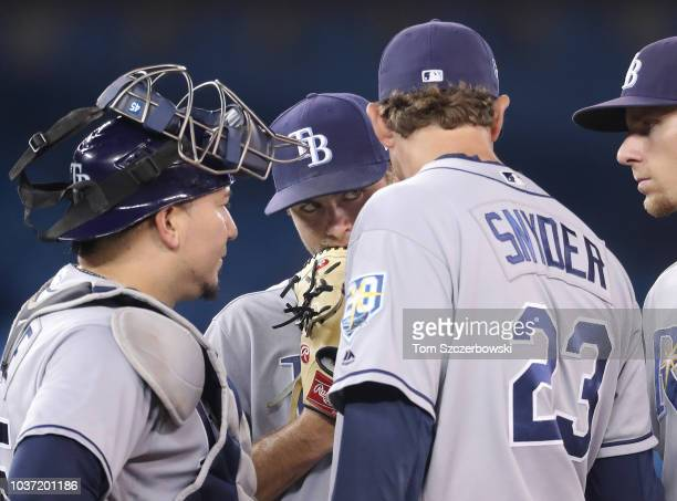 Jalen Beeks of the Tampa Bay Rays listens as he is visited on the mound by pitching coach Kyle Snyder as Jesus Sucre and Matt Duffy look on in the...