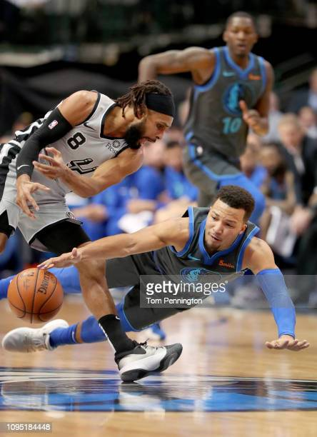 Jalen Brunson of the Dallas Mavericks dives for the ball against Patty Mills of the San Antonio Spurs in the first half at American Airlines Center...