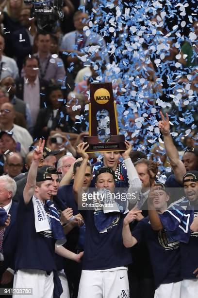Jalen Brunson of the Villanova Wildcats raises the trophy and celebrates with his teammates after defeating the Michigan Wolverines during the 2018...