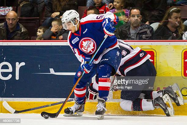 Jalen Chatfield of the Windsor Spitfires battles for the puck against Nick Moutrey of the Saginaw Spirit on December 18 2014 at the WFCU Centre in...