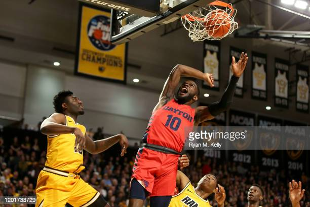 Jalen Crutcher of the Dayton Flyers reacts after dunking between Vince Williams and Jimmy Clark III of the VCU Rams in the first half during a game...