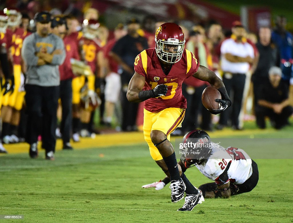 Jalen Greene #10 of the USC Trojans breaks the tackle of Brandon Cox #20 of the Arkansas State Red Wolves at Los Angeles Coliseum on September 5, 2015 in Los Angeles, California.