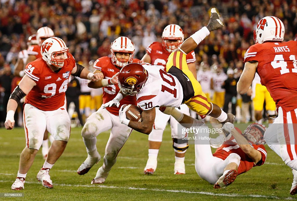 Jalen Greene #10 of the USC Trojans is upended while being tackled by Michael Caputo #7 of the Wisconsin Badgers and Conor Sheehy #94 of the Wisconsin Badgers during the second half of the National University Holiday Bowl at Qualcomm Stadium on December 30, 2015 in San Diego, California.