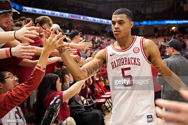 Jalen Harris of the Arkansas Razorbacks celebrates with the student section after a game against the Alabama Crimson Tide at Bud Walton Arena on...