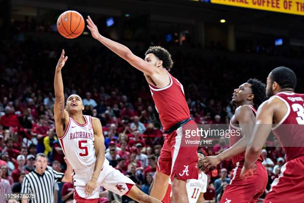 Jalen Harris of the Arkansas Razorbacks goes up for a shot and has it blocked out of bounds by Alex Reese of the Alabama Crimson Tide at Bud Walton...