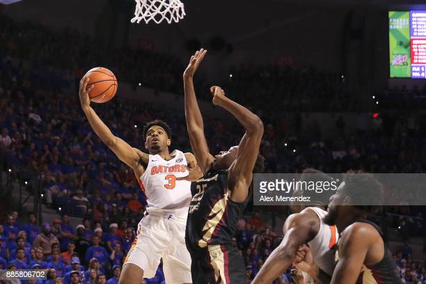 Jalen Hudson of the Florida Gators drives past Mfiondu Kabengele of the Florida State Seminoles during a NCAA basketball game at the Stephen C O'...