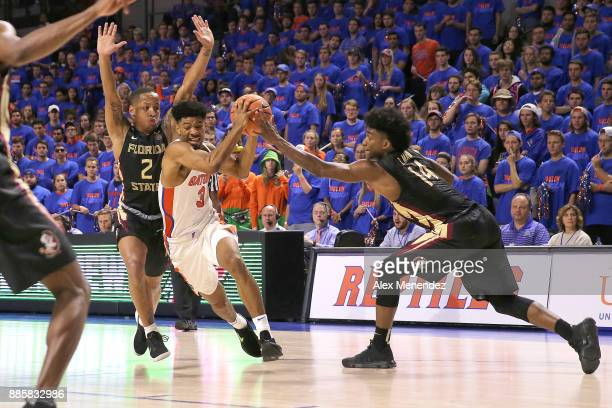 Jalen Hudson of the Florida Gators drives to the net against CJ Walker and Terance Mann of the Florida State Seminoles during a NCAA basketball game...