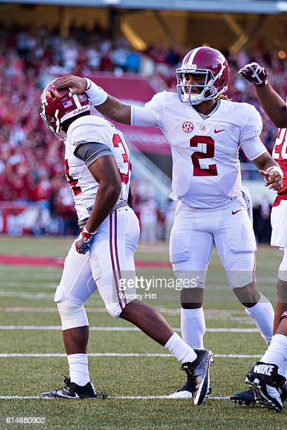 Jalen Hurts congratulates Damien Harris of the Alabama Crimson Tide after scoring a touchdown during a game against the Arkansas Razorbacks at...