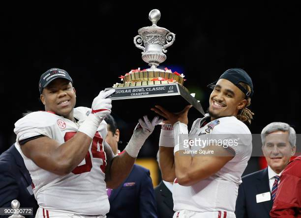 Jalen Hurts of the Alabama Crimson Tide and Da'Ron Payne celebrate with the trophy after the AllState Sugar Bowl against the Clemson Tigers at the...