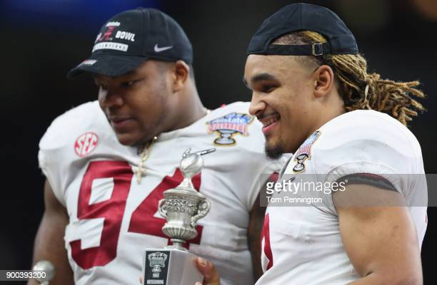 Jalen Hurts of the Alabama Crimson Tide and Da'Ron Payne celebrate with player of the game trophies after the AllState Sugar Bowl against the Clemson...