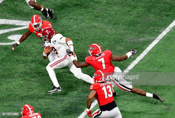Jalen Hurts of the Alabama Crimson Tide carries the ball against Lorenzo Carter and Roquan Smith of the Georgia Bulldogs in the CFP National...