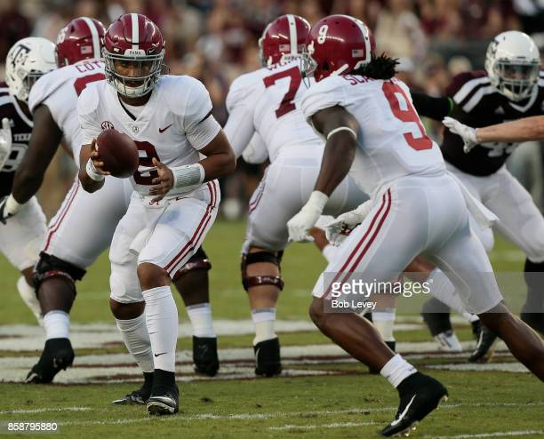 Jalen Hurts of the Alabama Crimson Tide hands off to Da'Shawn Hand in the first quarter against the Texas AM Aggies at Kyle Field on October 7 2017...
