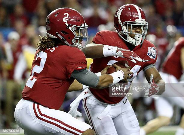 Jalen Hurts of the Alabama Crimson Tide hands the ball off to Damien Harris of the Alabama Crimson Tide during the 2016 ChickfilA Peach Bowl at the...
