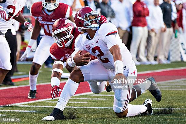 Jalen Hurts of the Alabama Crimson Tide is grabbed by the face mask by Da'Jon Harris of the Arkansas Razorbacks at Razorback Stadium on October 8...
