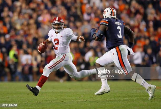 Jalen Hurts of the Alabama Crimson Tide is pursued by Marlon Davidson of the Auburn Tigers during the fourth quarter of the game at Jordan Hare...