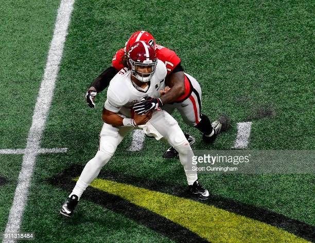 Jalen Hurts of the Alabama Crimson Tide is sacked by Davin Bellamy of the Georgia Bulldogs in the CFP National Championship presented by ATT at...