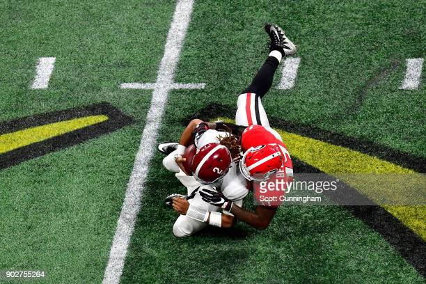 Jalen Hurts of the Alabama Crimson Tide is tackled by Davin Bellamy of the Georgia Bulldogs on a run during the second quarter in the CFP National...