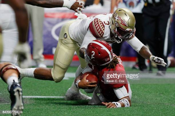 Jalen Hurts of the Alabama Crimson Tide is tackled by Derwin James of the Florida State Seminoles during their game at MercedesBenz Stadium on...