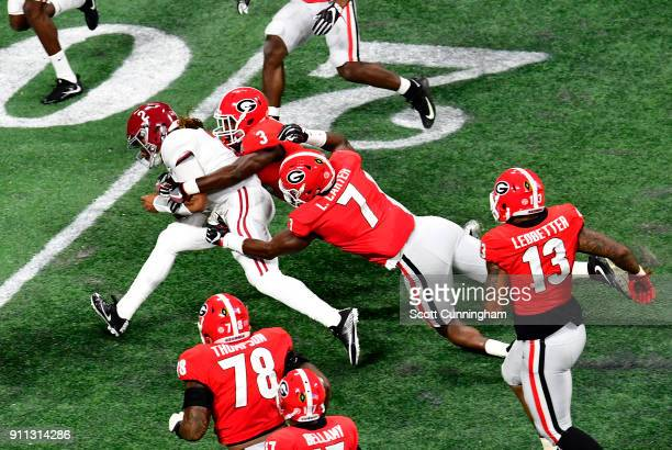 Jalen Hurts of the Alabama Crimson Tide is tackled by Lorenzo Carter and Roquan Smith of the Georgia Bulldogs in the CFP National Championship...