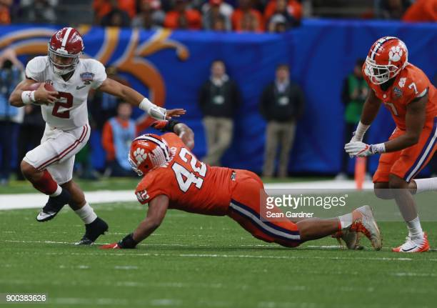 Jalen Hurts of the Alabama Crimson Tide run with the ball as Christian Wilkins of the Clemson Tigers defends in the second half of the AllState Sugar...