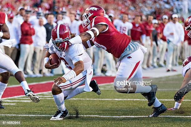 Jalen Hurts of the Alabama Crimson Tide runs for a touchdown and is grabbed by the face mask by De'Jon Harris of the Arkansas Razorbacks at Razorback...