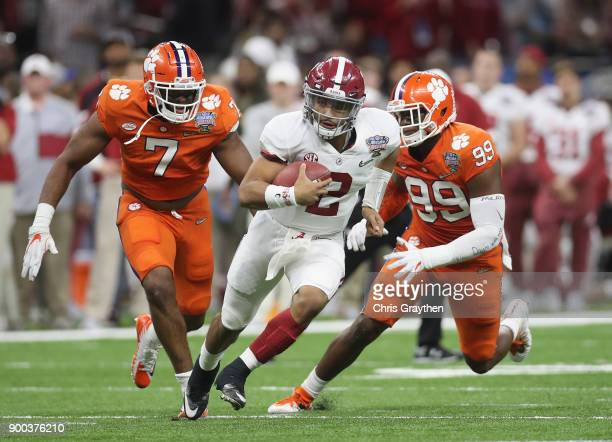 Jalen Hurts of the Alabama Crimson Tide runs with the ball as Clelin Ferrell of the Clemson Tigers and Austin Bryant defend in the first half of the...
