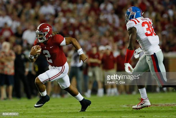 Jalen Hurts of the Alabama Crimson Tide rushes away from Marquis Haynes of the Mississippi Rebels at BryantDenny Stadium on September 30 2017 in...