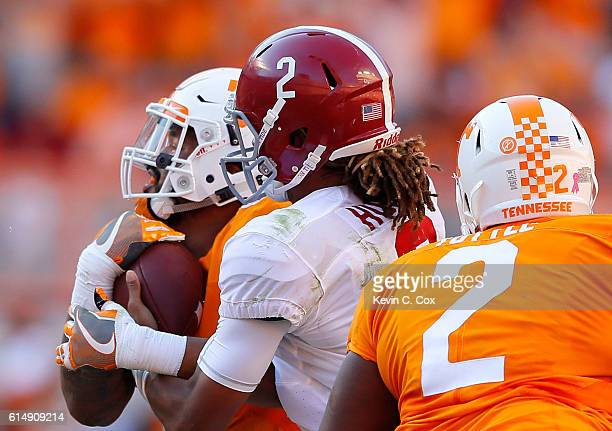 Jalen Hurts of the Alabama Crimson Tide tackles Derek Barnett of the Tennessee Volunteers after he intercepted Hurts' tipped pass at Neyland Stadium...