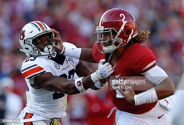 Jalen Hurts of the Alabama Crimson Tide tries to break a tackle by Johnathan Ford of the Auburn Tigers at BryantDenny Stadium on November 26 2016 in...